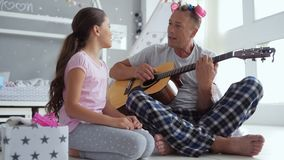 Cheerful cute little girl and her father singing song stock footage