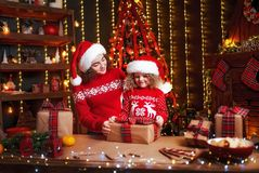 Cheerful cute little girl and her older sister exchanging gifts. stock image