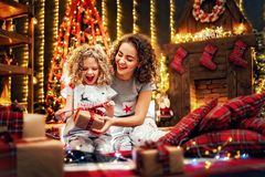 Cheerful cute little girl and her older sister exchanging gifts. Cheerful cute curly little girl and her older sister exchanging gifts. Sisters having fun near royalty free stock image