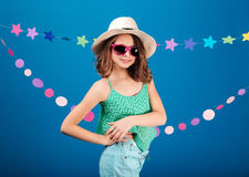 Cheerful cute little girl in sunglasses standing and posing Stock Photography