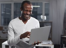 Cheerful cute manager is expressing gladness. Hilarious news. Portrait of overjoyed upbeat young african man is standing in cozy office and holding modern laptop stock images