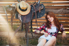 Cheerful cute redhead cowgirl resting at the ranch fence. Cheerful cute redhead cowgirl sitting and resting at the ranch fence Stock Photo