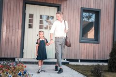 Cheerful cute schoolgirl holding hand of her young father going to school stock photo
