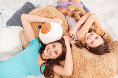 Cheerful cute sisters lying on soft plush bear at home Royalty Free Stock Photography