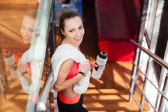 Cheerful cute woman athlete holding bottle of water in gym Royalty Free Stock Images