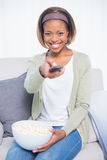 Cheerful cute woman sitting on sofa changing tv channel and holding popcorn Stock Image