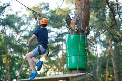 Cheerful cute young boy in blue t shirt and orange helmet in adventure rope park at sunny summer day. Active lifestyle, sport. Holidays for children stock images