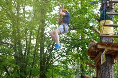 Cheerful cute young boy in blue t shirt and orange helmet in adventure rope park at sunny summer day. Active lifestyle, sport. Holidays for children stock image