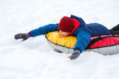 Cheerful cute young boy in orange hat red scarf and blue jacket holds tube on snow, has fun, smiles. Teenager on sledding. In winter park. Active lifestyle stock image
