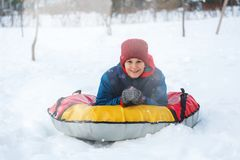 Cheerful cute young boy in orange hat red scarf and blue jacket holds tube on snow, has fun, smiles. Teenager on sledding. In winter park. Active lifestyle stock photography