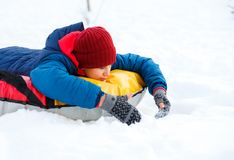 Cheerful cute young boy in orange hat red scarf and blue jacket holds tube on snow, has fun, smiles. Teenager on sledding. In winter park. Active lifestyle stock photo
