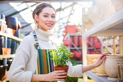 Cheerful cute young female gardener standing and choosing new pot Royalty Free Stock Photos