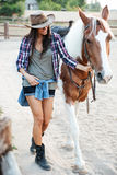 Cheerful cute young woman cowgirl walking with her horse Stock Photos