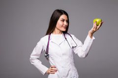 Cheerful cute young woman doctor standing and holding an apple over grey background Stock Photo