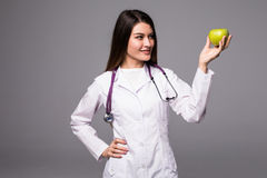 Cheerful cute young woman doctor standing and holding an apple over grey background Royalty Free Stock Photography