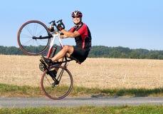 Cheerful cyclist balanced on the rear wheel. Stock Photos