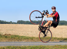 Cheerful cyclist riding on the rear wheel. Royalty Free Stock Photos