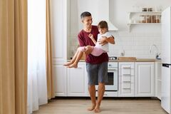 Cheerful dad carrying his dark haired daughter, playing with happy little preschool child indoors against kitchen set, playful