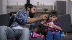 Cheerful dad and kid creating toys from blocks stock footage