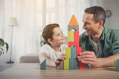 Cheerful dad and kid enjoying game at home. We did it together. Portrait of joyful father and son looking at each other with satisfaction while sitting near self Stock Photo