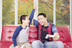 Cheerful dad playing video game with his son Royalty Free Stock Images