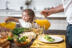Cheerful dad serving healthy drink for his daughter stock photo