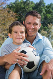 Cheerful dad and son with football. Cheerful dad and son smiling with a football at the camera in park Royalty Free Stock Image