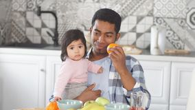 Cheerful daddy having fun with fruit at home. Happy guy with a kid in hand holding an apple in front of his eyes stock video footage
