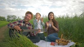 Cheerful daddy plays musical instrument while mom with son enjoy and applaud while relaxing on family picnic in nature. In green field close-up stock video