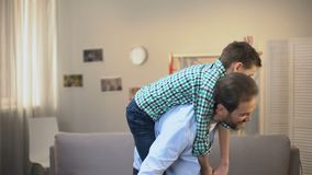 Cheerful daddy and son playing airplane, happy family moments, childhood. Stock footage stock video