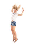 Cheerful dancing girl jumping short on white background flying hair Stock Image