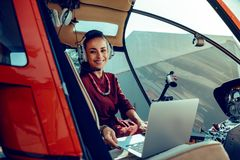 Cheerful dark-haired woman with wide smile placing silver laptop on front seat stock photography