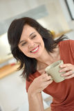 Cheerful dark-haired woman woth cup of tea Stock Images