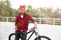Cheerful dark skinned man standing near his bicycle. Picture of cheerful dark skinned man wearing cap standing near his bicycle. Against nature background Stock Photos