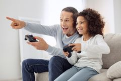 Cheerful daughter and father playing a game. Joyful game. Pretty exuberant curly-haired girl smiling and playing games with her father while sitting on the couch Royalty Free Stock Photography