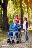 Cheerful daughter and grandchildren visiting disabled father in. Cheerful daughter and grandchildren visiting senior disabled father in park Royalty Free Stock Photo