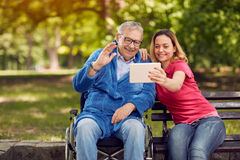 Cheerful daughter with her disabled father in wheelchair using a Stock Photo