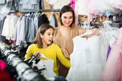 Cheerful daughter with mother are looking for pretty dresses Royalty Free Stock Images