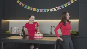 Women preparing for celebration of mom`s Birthday. Cheerful daughters waiting for beloved mother while serving kitchen table with champagne and festive decorated stock footage