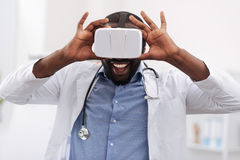 Cheerful delighted doctor using virtual reality glasses Royalty Free Stock Photo