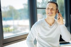 Cheerful delighted man listening to his interlocutor. Mobile communication. Cheerful delighted attractive man putting a phone to his ear and smiling while Stock Images