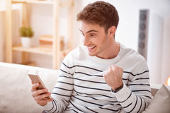 Cheerful delighted man sitting on the sofa. Taste of gladness. Cheerful positive smiling man sitting on the couch and holding cell phone while expressing joy stock photography