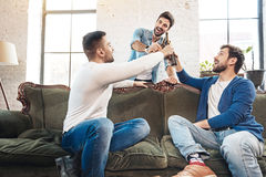 Cheerful delighted men raising bottles with beer. Time for a toast. Cheerful delighted brutal men raising bottles with beer and saying a toast while resting Stock Photos