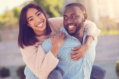 Cheerful delighted woman holding on to her boyfriend. He is strong. Cheerful delighted young women holding on to her boyfriend and laughing while being carried Royalty Free Stock Image