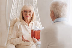 Cheerful delighted woman receiving a present. Such a surprise. Cheerful delighted senior women smiling and looking at her husband while receiving a present from Royalty Free Stock Photo