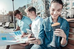 Cheerful delighted woman smiling. Positive emotions. Cheerful delighted beautiful women using her smartphone and smiling while drinking coffee Stock Photo