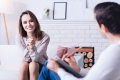 Cheerful delighted woman smiling. Positive emotions. Cheerful delighted cute women smiling and looking at her psychologist while being in a good mood royalty free stock photo
