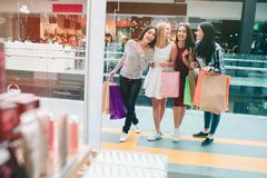 Cheerful and delightful young women are standing at entrance of store and looking inside it. They are very happy and stock photography