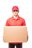 Cheerful delivery man happy young courier holding a cardboard box and smiling while standing on white background Stock Photos