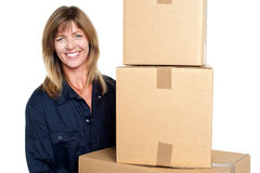 Cheerful delivery woman carrying sealed cartons Royalty Free Stock Image